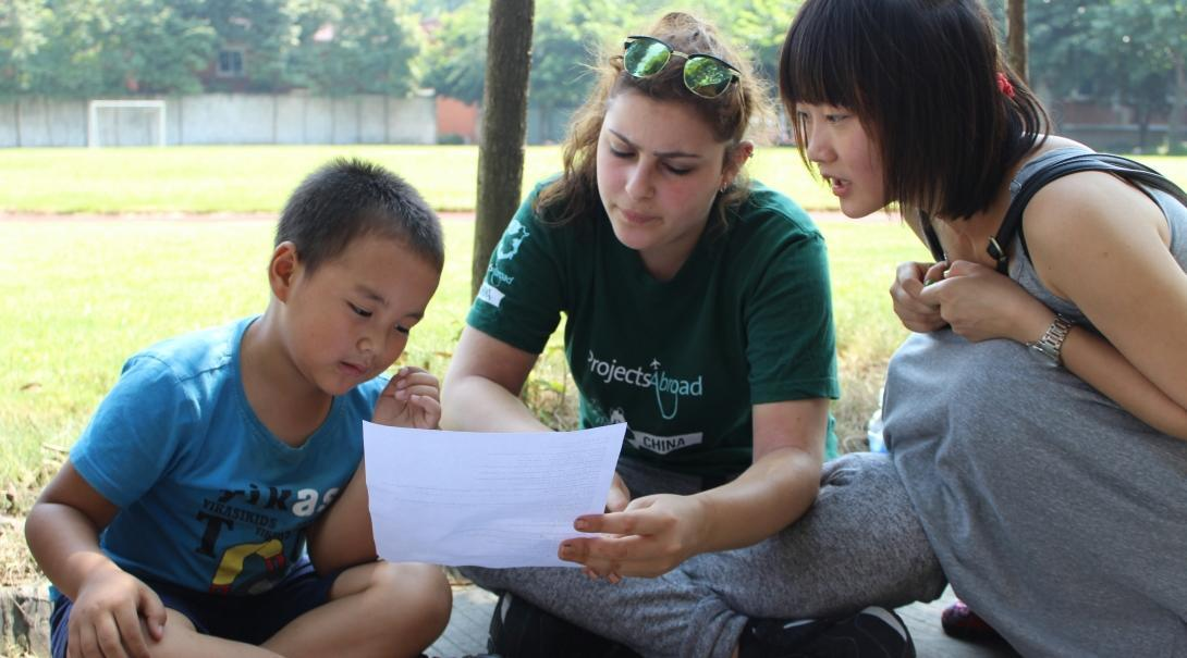 A Teaching volunteer in China helps her student learn the lines of an English play